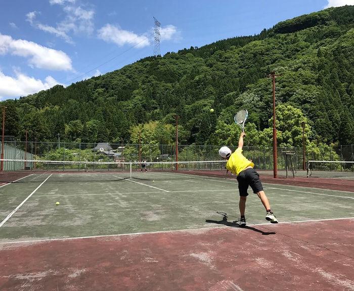 テニスコートでテニスをしている人の写真