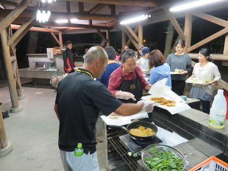 炊事場で料理をしている人達の写真