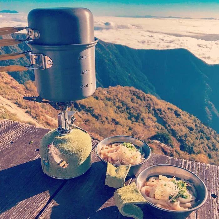 テーブルにシェラカップとガス缶が置いてある写真