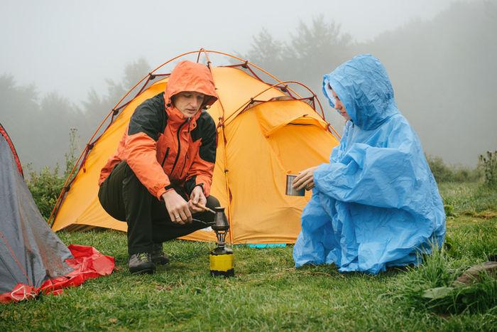 雨が降っている中のキャンプでかっぱを着てランタンをつけようとしている人たちの写真