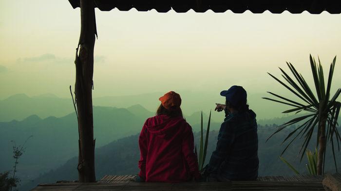 山の高台の屋根小屋から景色を見ている二人の写真