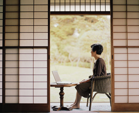 縁側でパソコンを開いている女性の写真