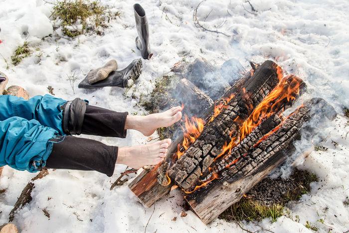 足を焚き火で温めている人の写真