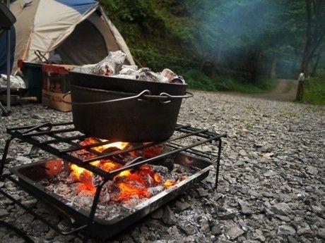 キャンプで炭を焚いて鍋を温めている様子の写真