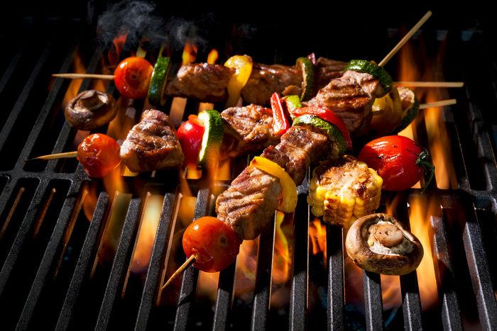 バーベキューコンロで串焼きを焼いている写真