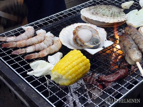 バーベキューで海鮮や野菜を焼いている写真