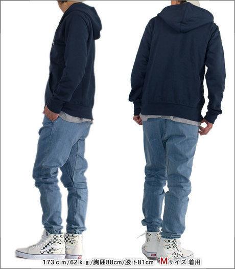デニムカラーのパンツを履いてラフなコーデをしている男性の写真