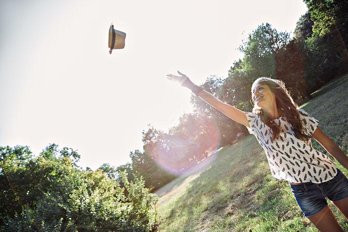 ハットを空に投げている女性の写真