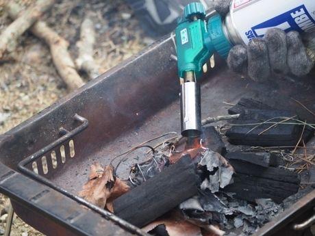 バーベキューコンロで炭起こしをしている写真