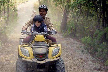 バギーに乗って山道を走っている親子の写真