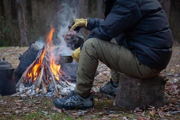 焚き火用手袋をつけてシェラカップにお湯を入れている写真