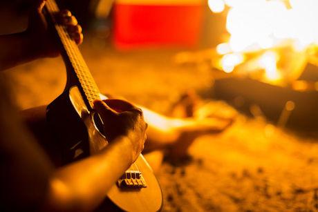 焚き火のそばでウクレレを引いている写真