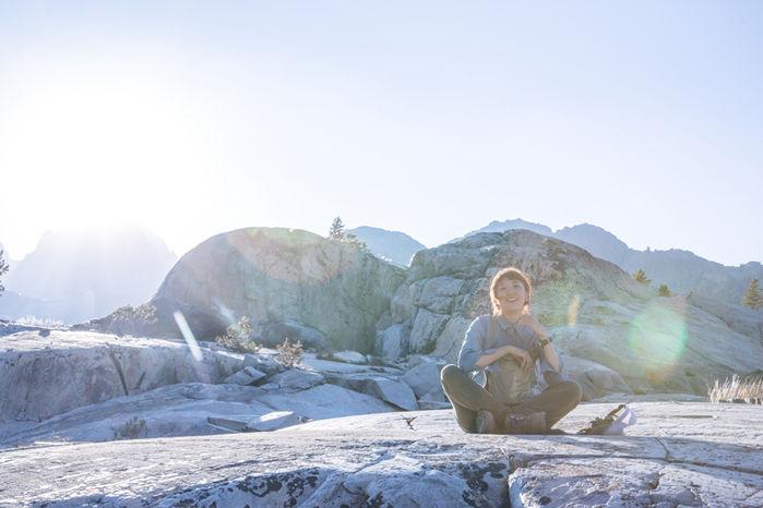 岩の上に座っている女性の写真