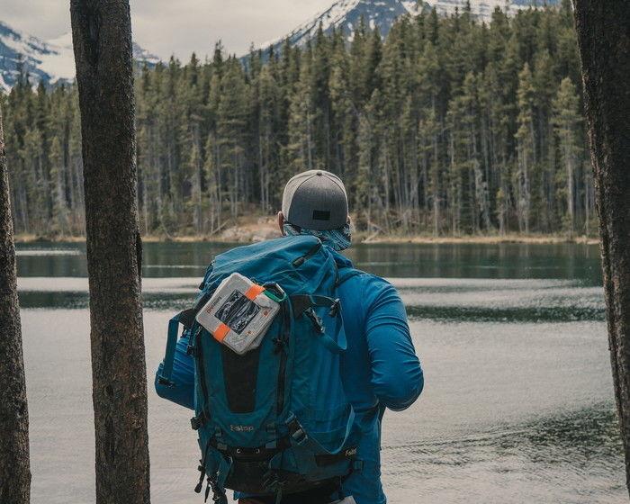 リュックを背負って川を見ている男性の写真