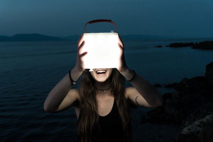 ソーラーランタンを持っておる女性の写真