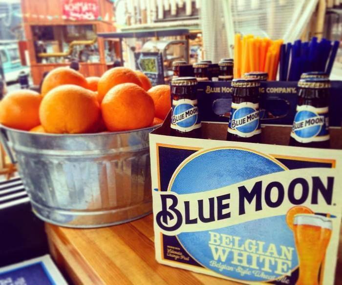 瓶ビールとバケツに入ったオレンジの写真