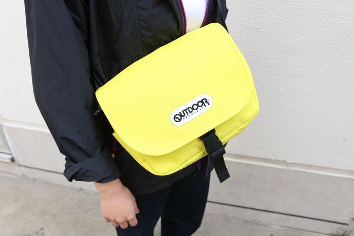 ライトイエローのアウトドアブランドのバッグをかけている女性の写真