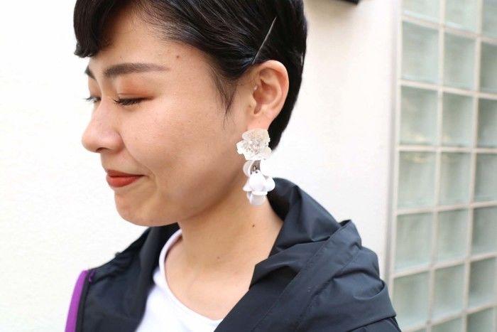 白い花のピアスをつけている女性の写真