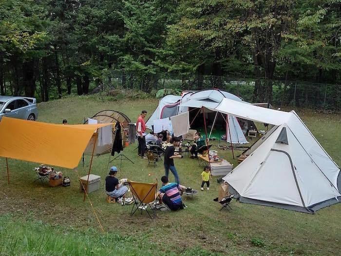 フリーサイトにテント貼ってキャンプをしている人の写真