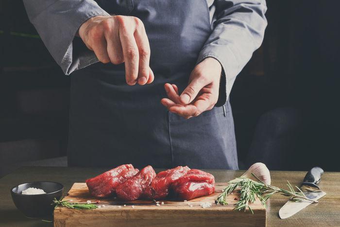肉に塩をまぶして下味をつけている様子