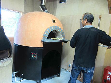 ピザ窯でピザを焼く様子