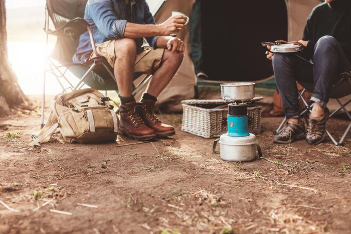 ストーブを囲んでキャンプをしている写真