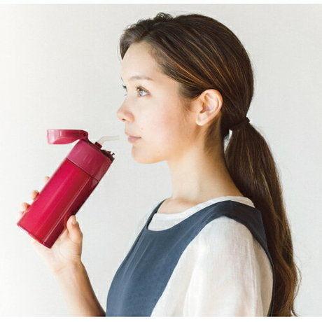 サーモスのストローマグで飲み物を飲む女性