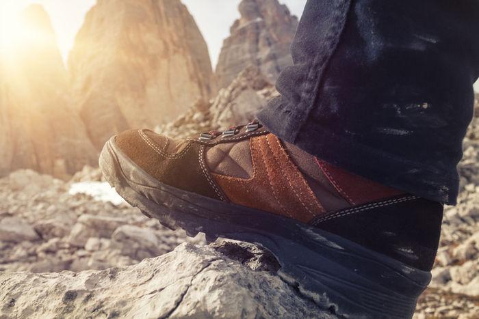 トレッキングシューズを履いて岩に足を乗せている写真