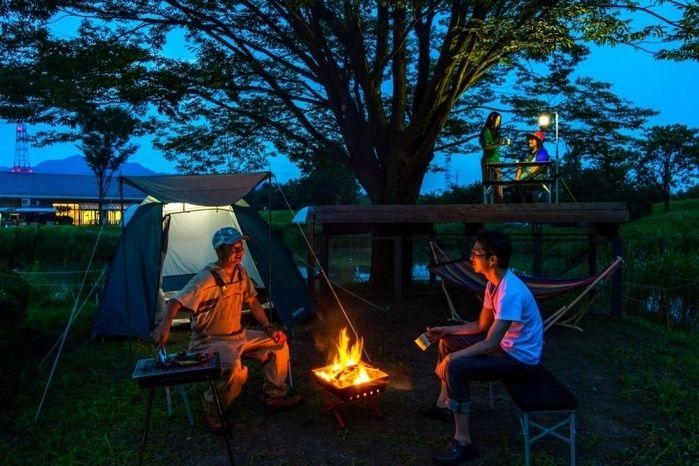 キャンプで焚き火をしている二人の男性
