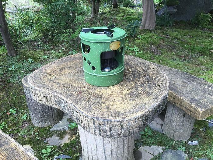 木のテーブルの上に置いてあるだるまストーブ