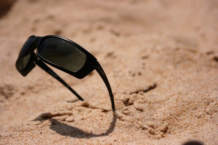 砂浜に刺さってるサングラスの写真
