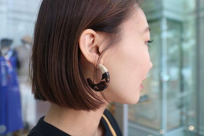 茶色のシックで落ち着いたデザインのイヤリングを付けている女性の写真