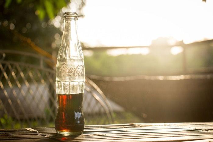 テーブルに瓶コーラが置いてある画像