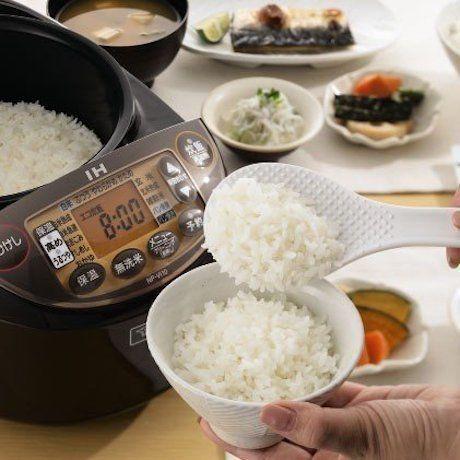 炊飯器からご飯をよそっている写真