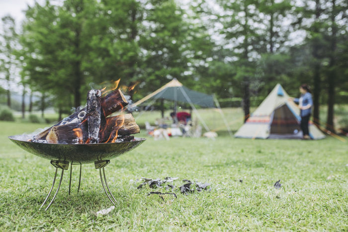 キャンプのテントサイトで焚き火をしている写真