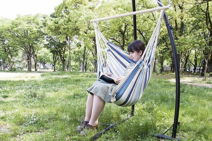 ハンモックに座って本を読んでいる女性の写真