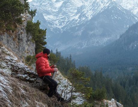 ダウンジャケットを着て山を眺めている男性
