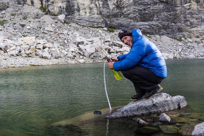 ダウンジャケットを着て川で遊んでいる男性