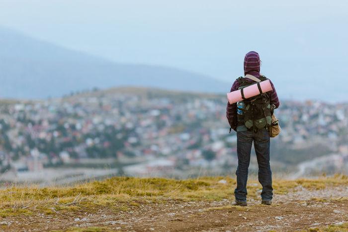 丘の上から綺麗な景色を見ている人の写真