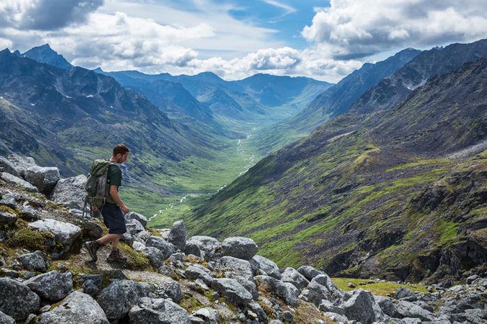 リュックを背負って山を降る男性