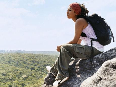 リュックを背負って岩の上に座っている女性の写真