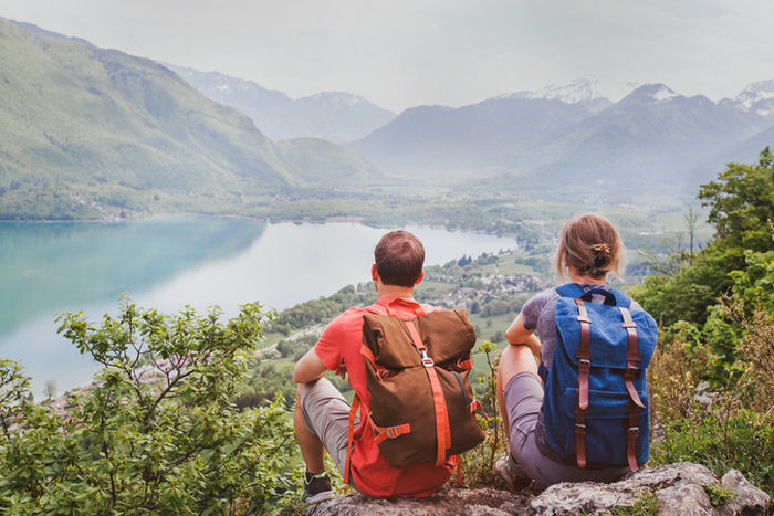 リュックを背負って景色を眺めている夫婦
