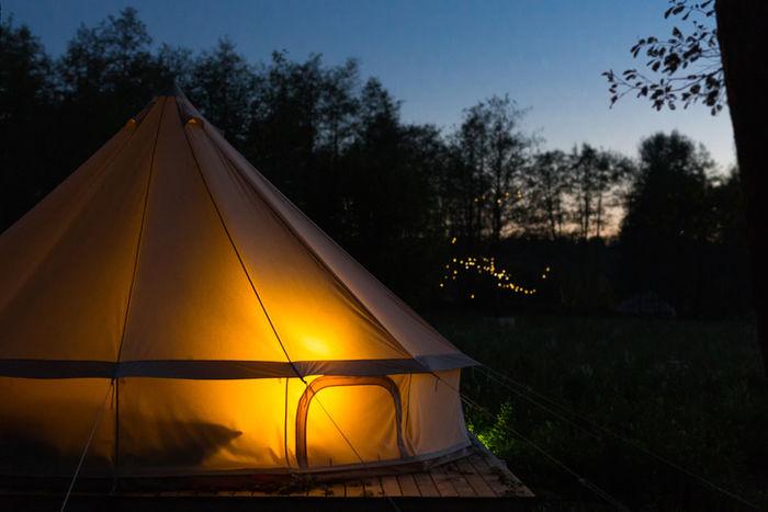 明け方に灯りの灯ったテントの写真