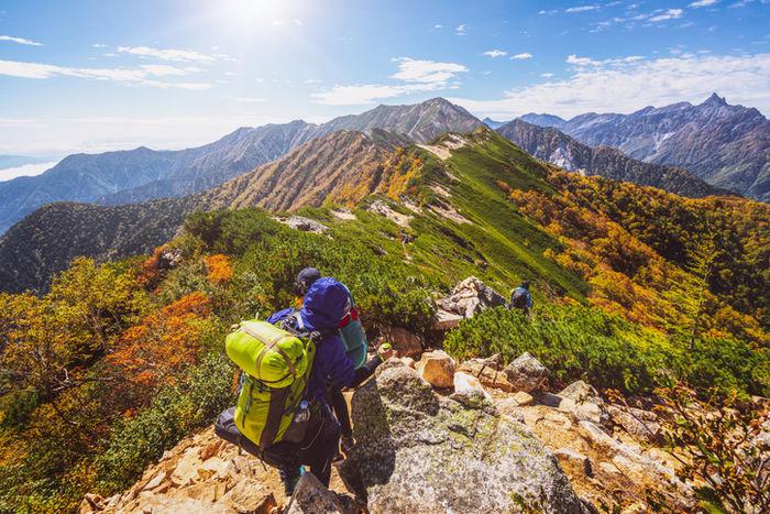 アウトドアバッグを背負って登山している人の様子