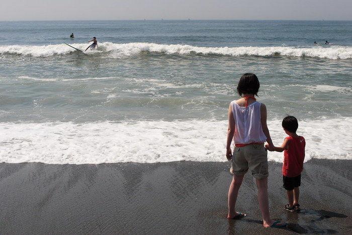 海沿いで海を眺める兄妹の写真