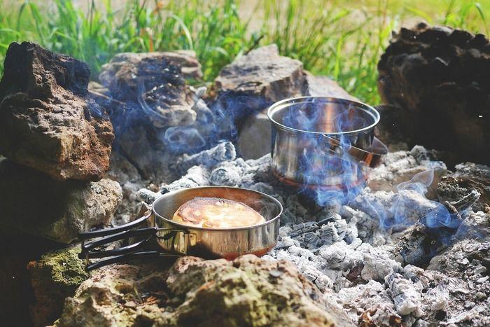 石の上で火を起こし料理をしている写真