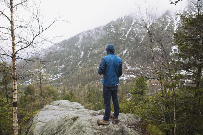 岩の上で佇んでいる男性の写真