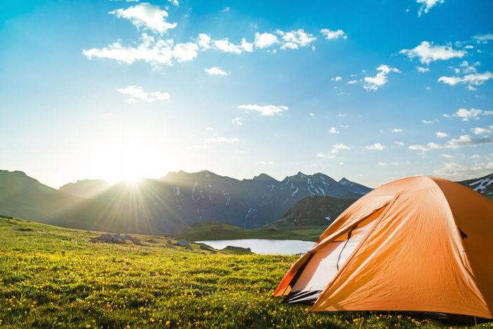 草原に張ってあるオレンジ色のテントの写真