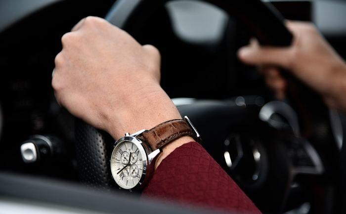 腕時計を付けて車を運転している写真