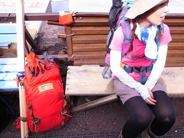 リュックを背負ってベンチで休憩している女性の写真